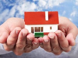 photo of model home held in pair of hands